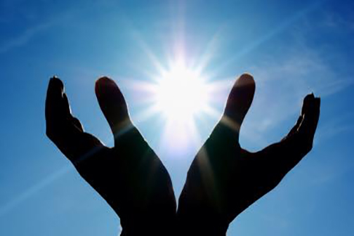 [Photo of the sun seen through open hands]
