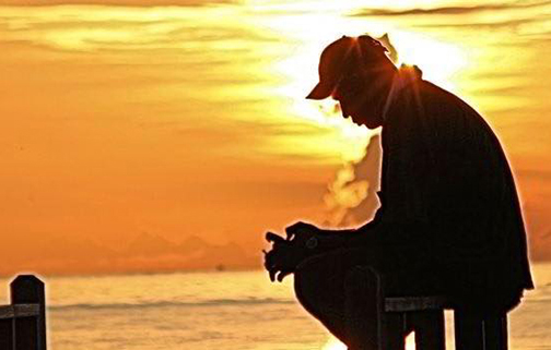 [Photo of man sitting on a dock in the early morning light]