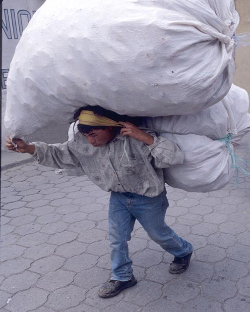 [Photo of a man carrying a large load]