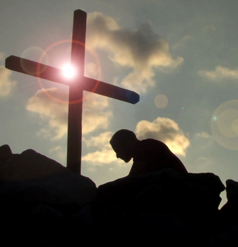 [Photo of a man kneeling at the foot of a cross]