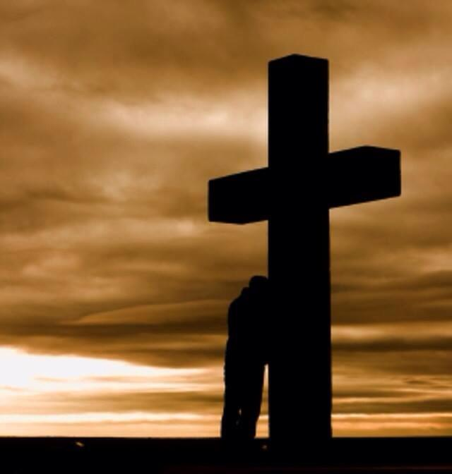 [Photo of a man leaning against a large cross]