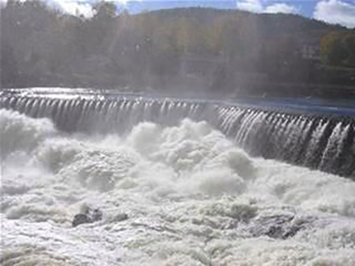 [Photo of water flowing over a dam]