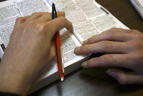 [Photo of a person writing in the Bible]